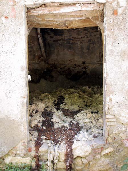 Open deur van vervallen gebouw, resten schapenwol binnen