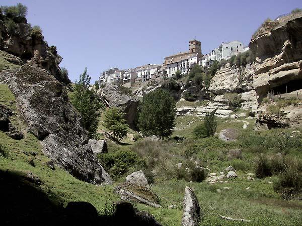 Witte huizen en bakstenen kerk van Alhama de Granada vanuit de kloof gezien