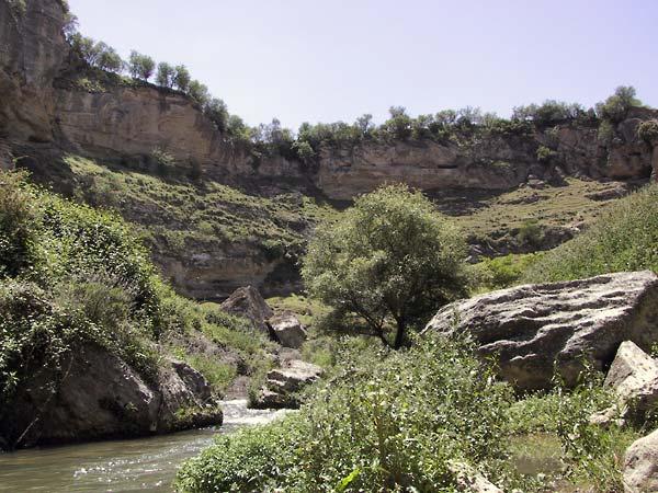 Water, struiken, rotsblokken en okergele rotswanden