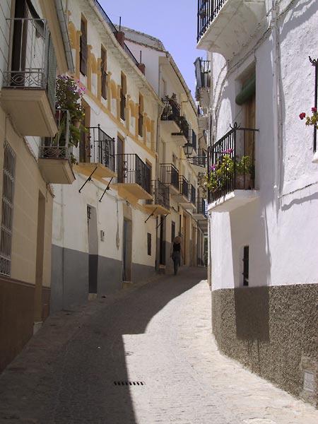 Steeg in bocht, witte huizen met okeren accenten