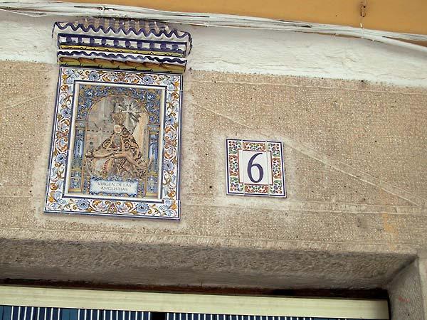 Een heilige in tegelwerk (met dakje in tegenwerk), met huisnummer in tegelwerk ernaast