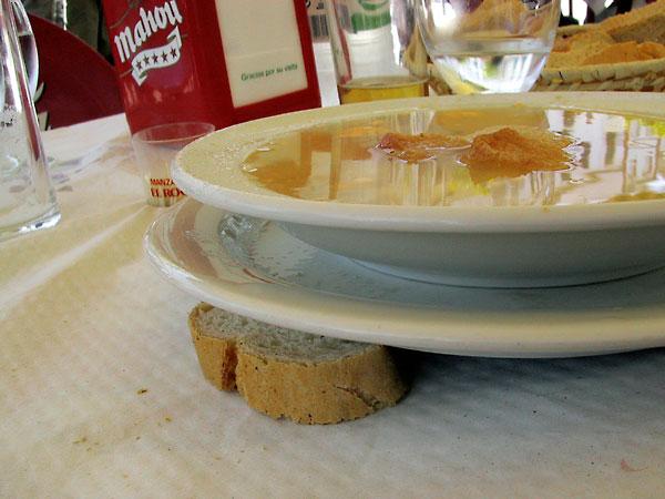 Bord met soep, aan 1 kant ondersteund door stuk brood