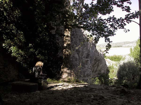 Sylvia in de schaduw op stenen bankje aan het schrijven