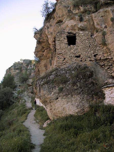 Gemetselde muur met opening in rotswand