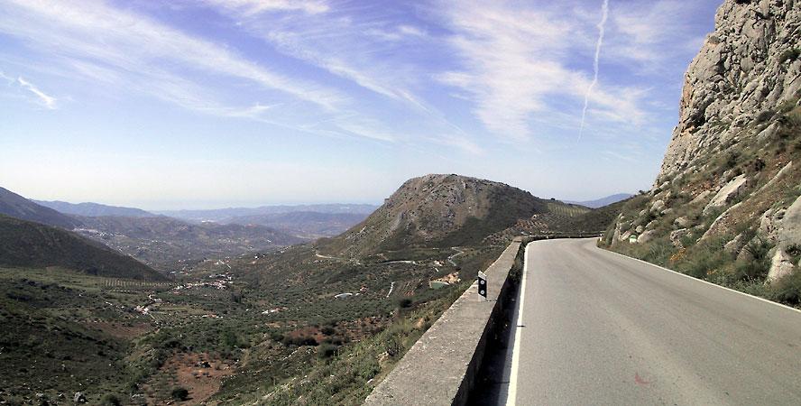 Mooie asfaltweg langs rotswand, links dal en heuvels