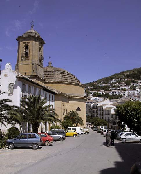 Straat met witte huizen, palmen, en kerk met koepel