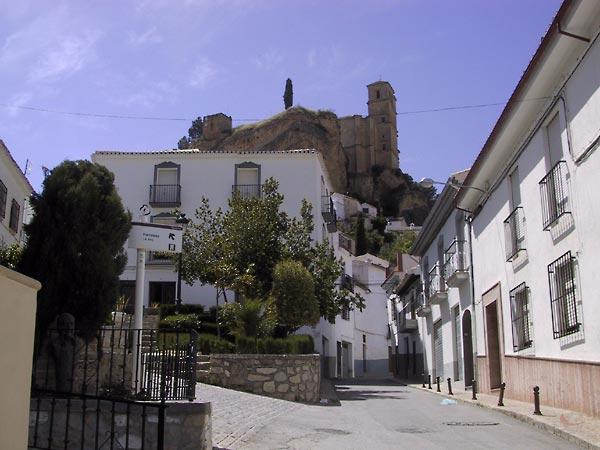 Straat met witte huizen en hoog daarboven een kasteel