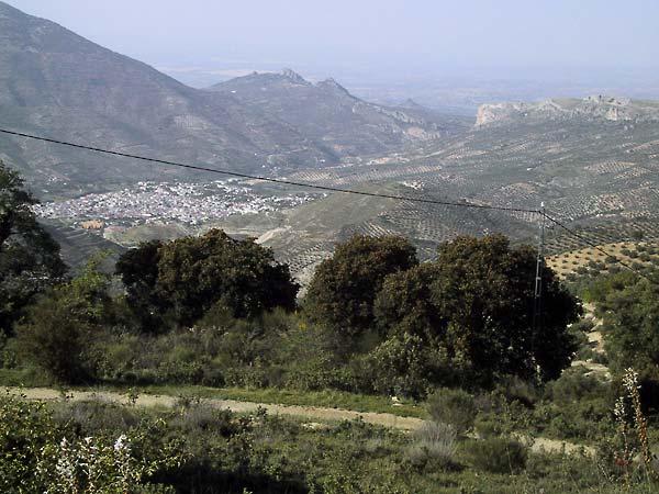 Van hoog zicht op wit stadje met poort in de bergen naar vlakte