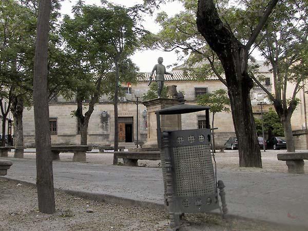 Plein met bomen, stenen banken, renaissancehuizen, en een beeldje