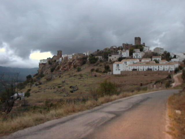 Bovenop berg: wit dorpje met bruine torens