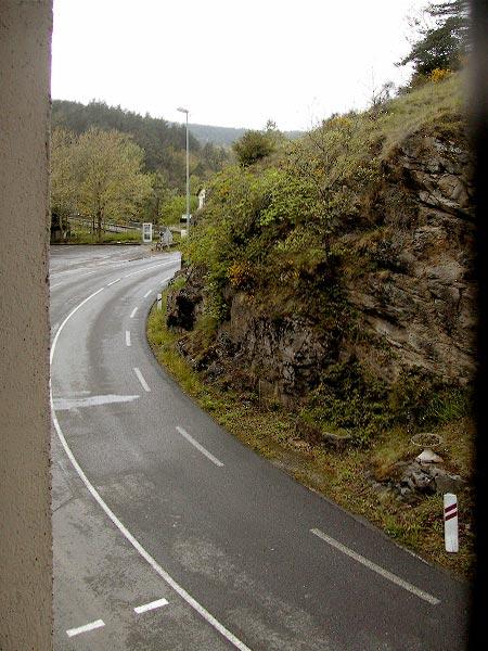 Van boven zicht op natte weg met loodrechte rotswand ernaast