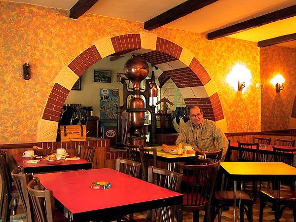 Formica tafeltjes, een ronde boog, een koperen apparaat, nepbalken aan het plafond