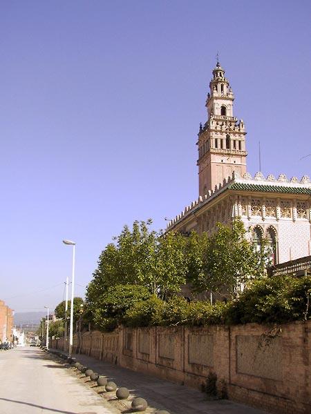 Achter een muur een Moors aandoend gebouw met toren die op een kleine Giralda lijkt