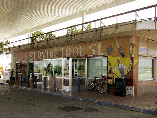 Benzinepomphuis, betegeld, met voorstellingen van pompbedienden aan het werk