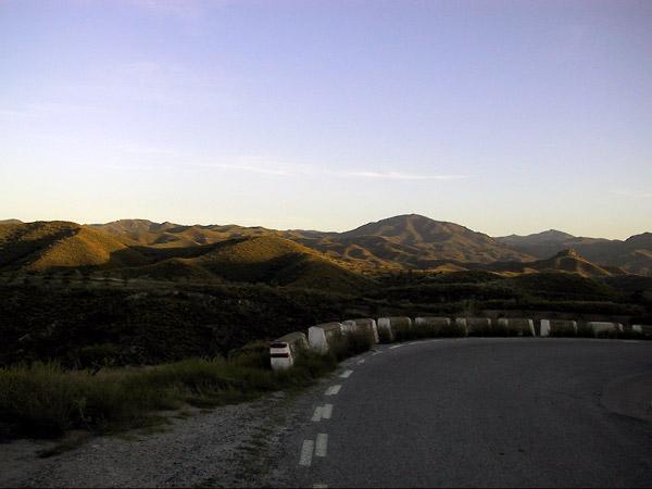 De weg in de schaduw, de toppen van de donkergroene bergen in de zon