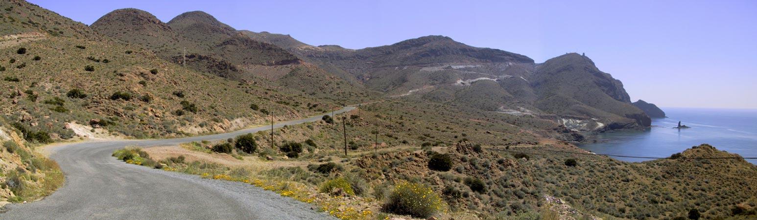 Vanaf de weg rechts beneden de zee, voor je bochten, in de met lage struiken en bloemen begroeide bergen
