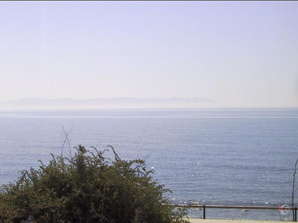 Rustige zee met enorme kaap in de verte