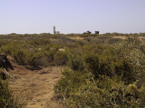 Zand, struikjes, twee motoren en een kerkje op de achtergrond