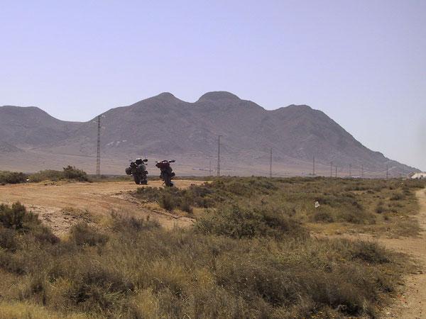Motoren op een zandweg met bergen op de achtergrond