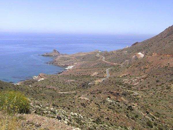 Berghellingen lopen uit in zee, met weggetje over de flanken