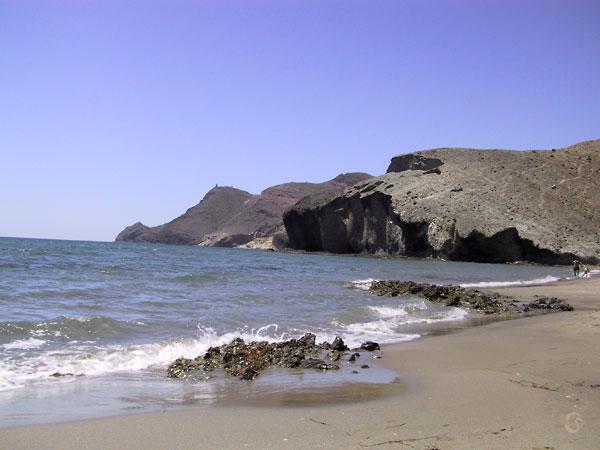 Strandje met in zee uitstekende zwarte rotsen