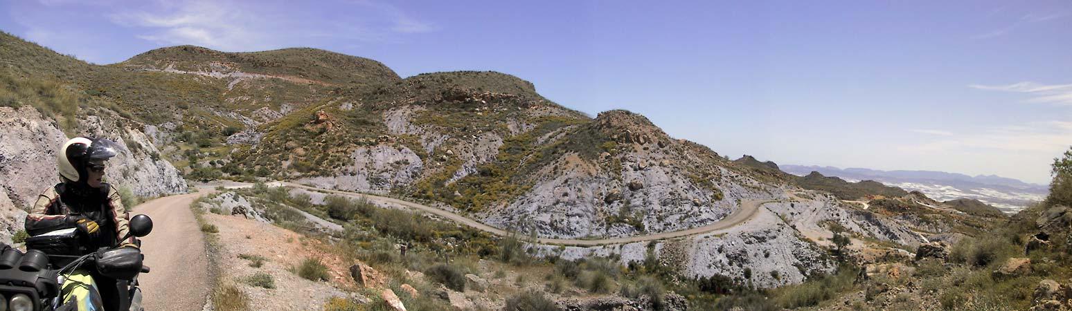 Syl uitkijkend over dal, op weg die zich langs woeste berghelling slingert