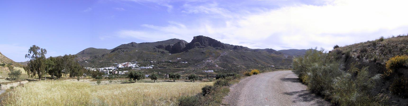 Zwarte bergen, terrassen op de hellingen, en wit stadje onderaan