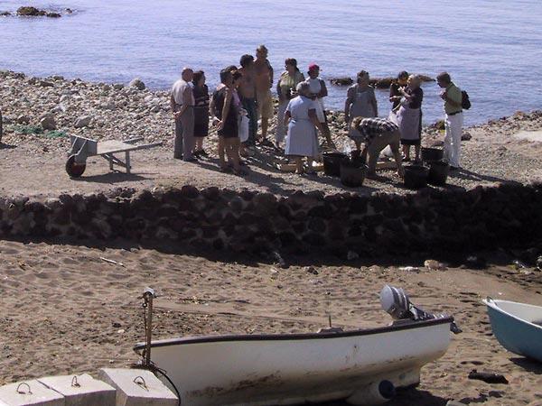 Emmers met vis op de pier, dorpsbewoners en toeristen er omheen