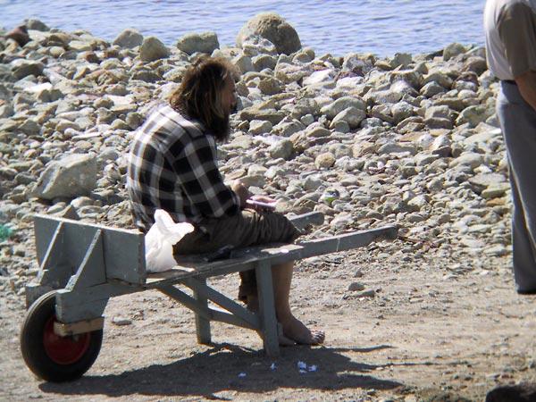 Man met baard en blote voeten zit samen met zijn plastic zak op kruiwagen