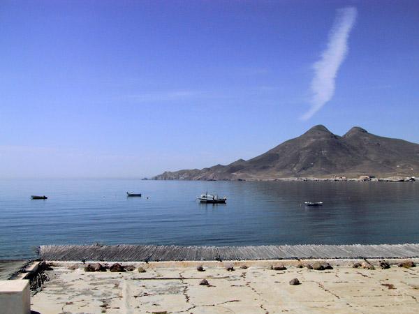 Vissersboten op kalme zee, met vulkanische bergen op de achtergrond