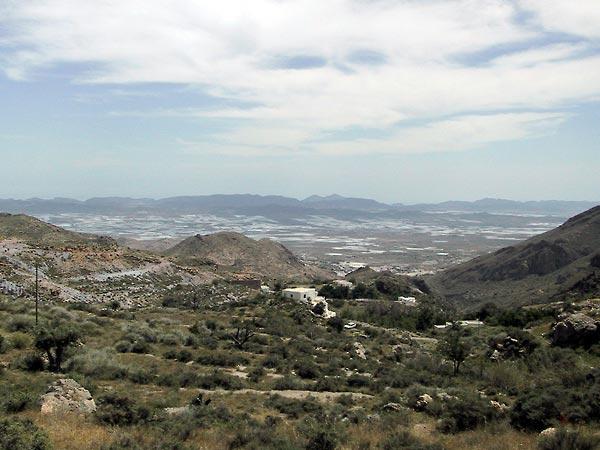 Uitzicht over berghelling in terrassen, met in de verte plastic in het dal
