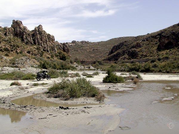 Resten van een dam tussen hogere rotsen, en de modderige resten van het stuwmeer