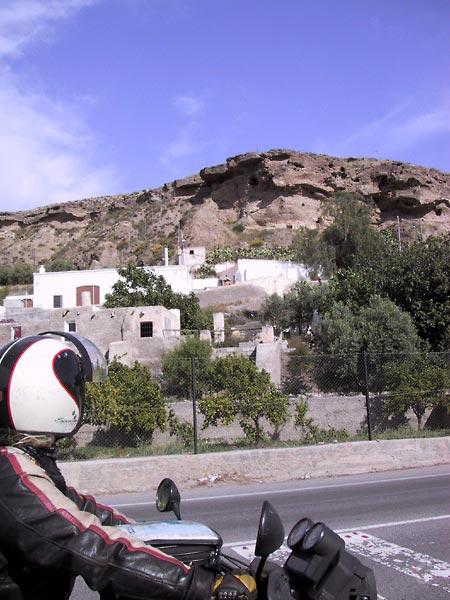 Sylvia kijkt naar witte huizen aan de voet van een donkerrode rots