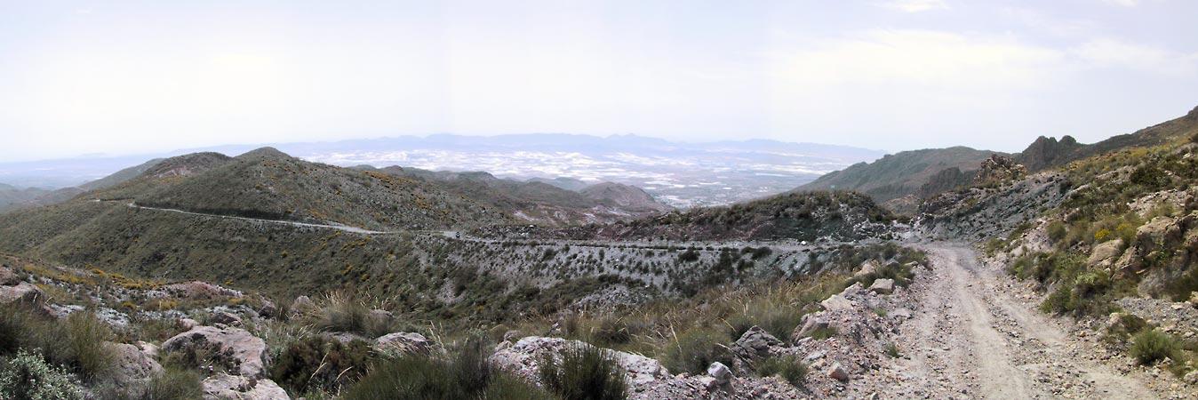Weg van grijs puin door de Sierra Alhamilla met de plastic zee op de achtergrond