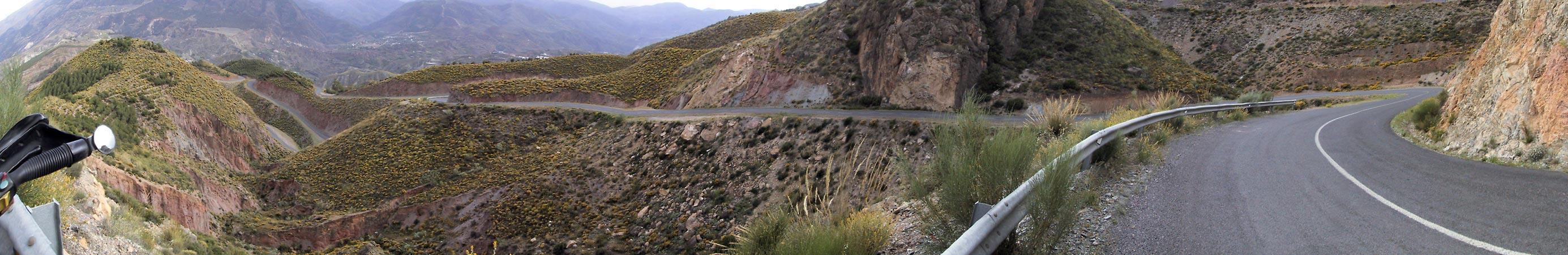 Steile rode ros=tsen, groen-geel negroeid waar het vlakker is, en een kluwen van een weg daar doorheen