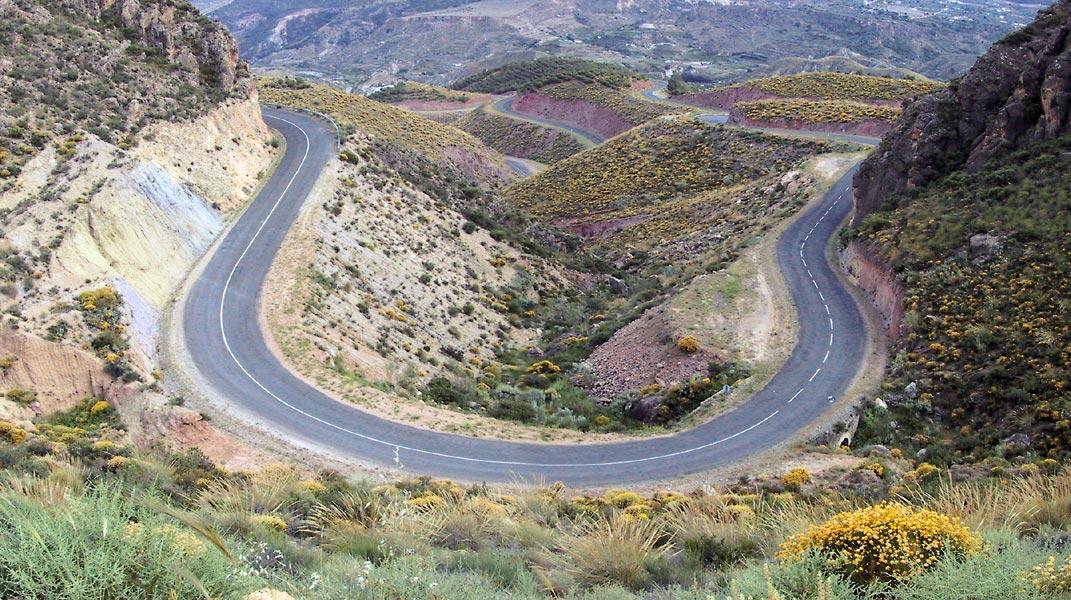De weg van boven gezien, de rotsen blauw, geel en rood, de brem geel