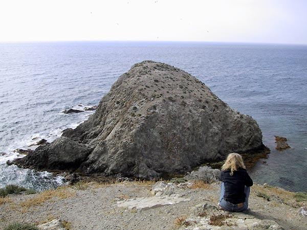Sylvia op de rug gezien, zittend, uitkijkend over de zee met het eilandje van de moor