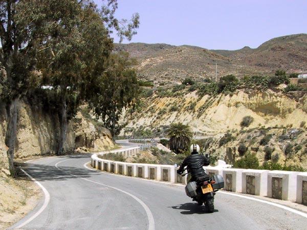 Bochtige asfaltweg langs gele rotsen