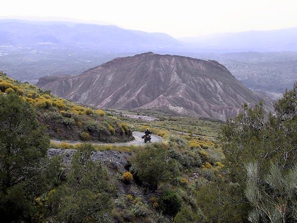 Bochtje naar beneden tussen gele struiken met uitzicht over bergen in kleurige steen