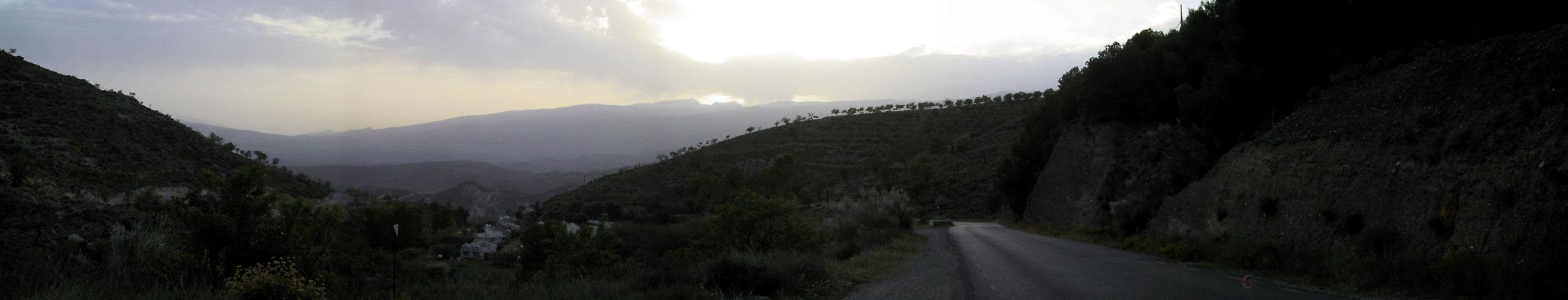 Weg door golvend landschap, naaldbomen, lila avondlucht, en wit dorpje in het dal
