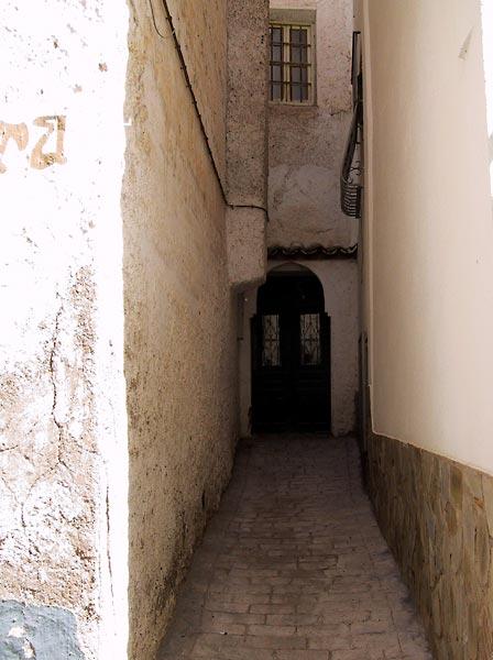 Heel smal steegje tussen witte muren naar één voordeur