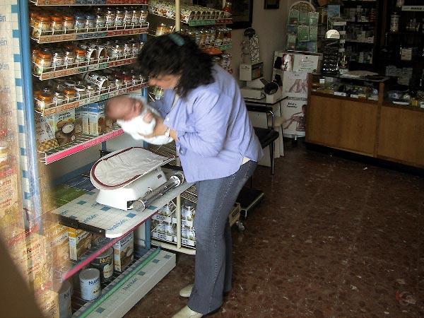 Baby wordt op weegschaal gelegd in de apotheek