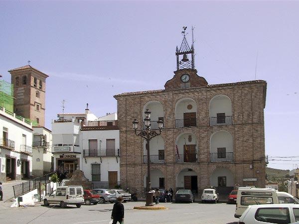 Pleintje met gemeentehuis, boogvormige openingen in bakstenen gevel voor de galerijen daarachter in drie verdiepingen