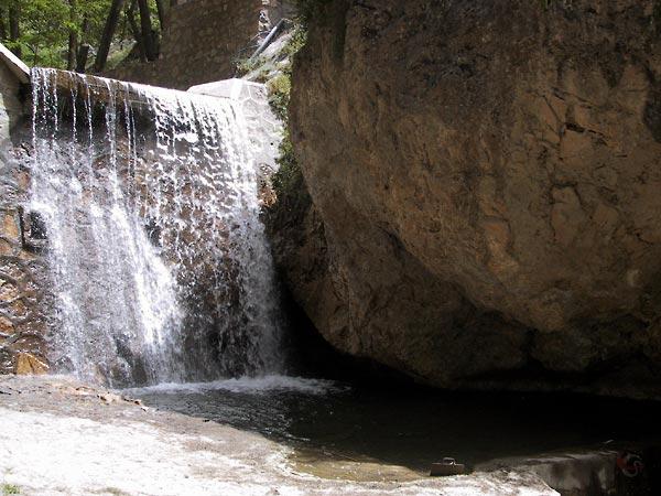 Kaarsrechte waterval tussen rode rotsen en naaldbomen
