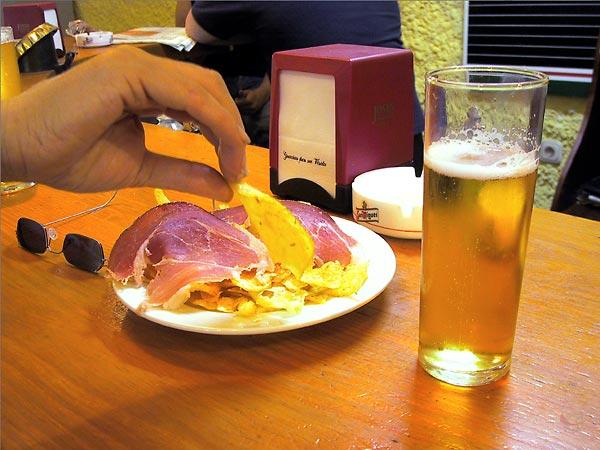 Glas bier, bordje met chips en Serrano ham
