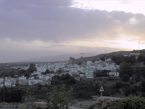Witte huizen, kerk er boven uit torenend, en wat bouwkranen
