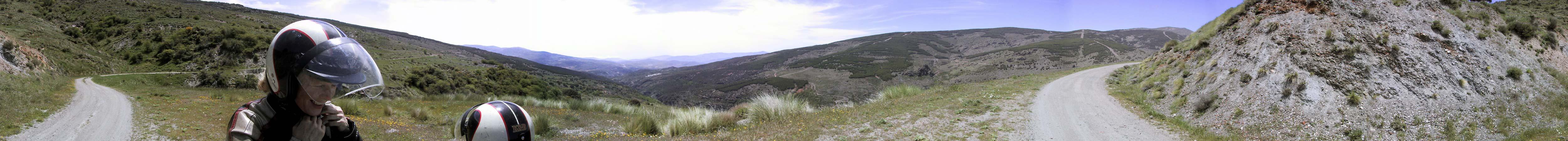 Onverharde weg langs spaarzaam begroeide berghelling, enorm uitzicht over de bergen