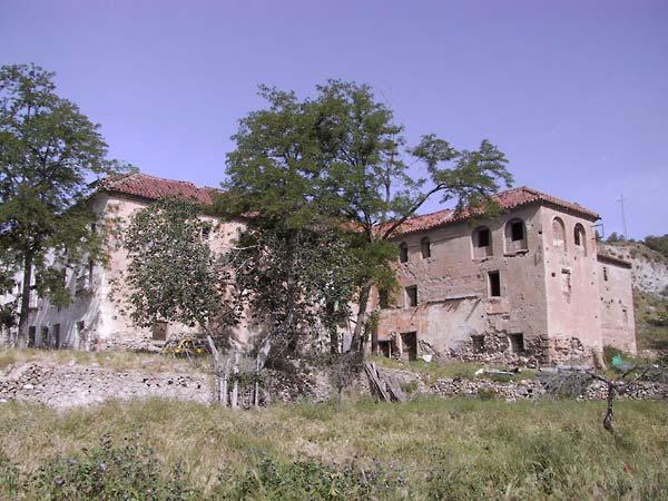 Groot vervallen klooster van baksteen met rood pannendak, op helling met muurtjes en verwaarloosde boomgaard