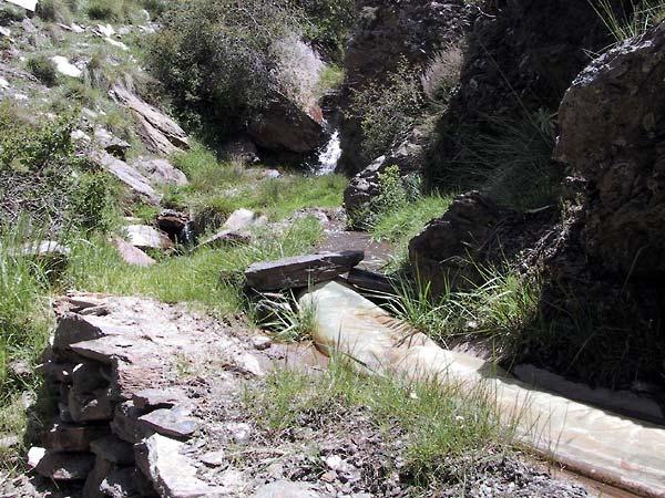 Grijze rotsblokken waartussen water naar beneden dendert