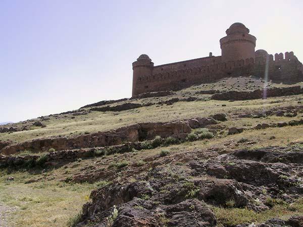 Het castillo van onderen: muur met kantelen en twee stoeren ronde torens in baksteen